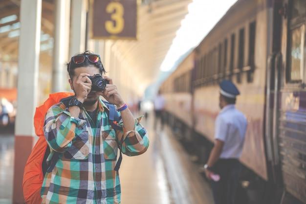 Los viajeros toman fotos de parejas mientras esperan los trenes.