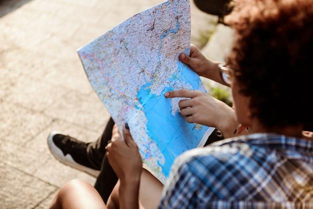 Los viajeros viendo la ruta en el mapa, sentado en el banco en el parque.