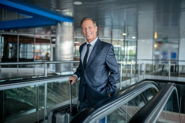 Viajes, aeropuerto. hombre feliz adulto atractivo en traje formal oscuro con maleta en la escalera mecánica del aeropuerto en estado de ánimo optimista