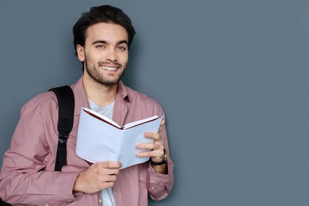 Viajes agradables. turista barbudo guapo alegre sonriendo y mirándote mientras sostiene una guía de viaje