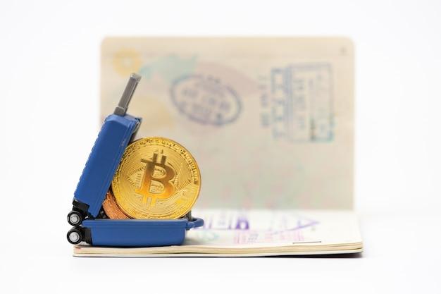 Viajes y ahorro financiero. equipaje en miniatura y, modelo bitcoin en el pasaporte.