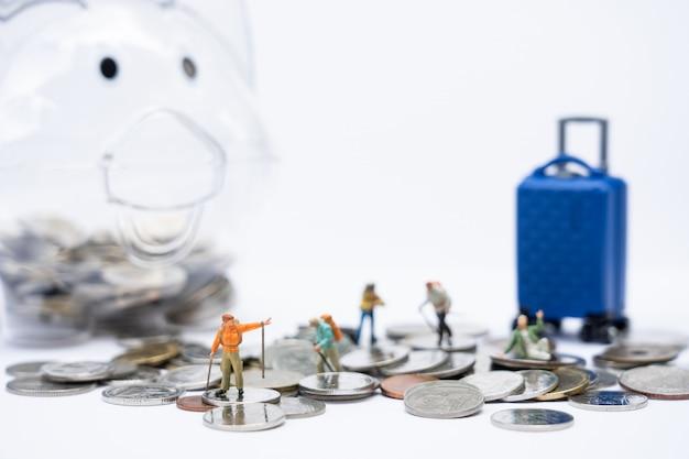 Viajes y ahorro. personas en miniatura, viajeros con mochila caminando sobre pilas de monedas y hucha y equipaje como telón de fondo.