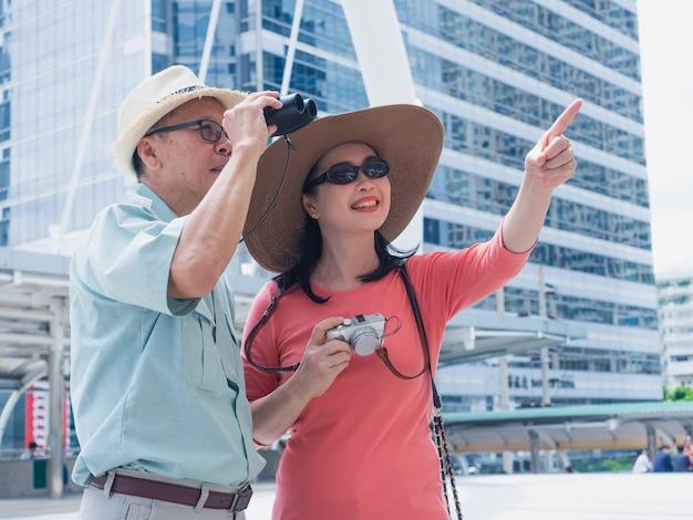Viajes de ancianos en la ciudad, hombre y mujer mayores buscando algo por binoculares en la ciudad