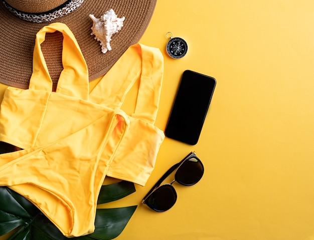 Viajes y aventuras. equipo de viaje plano con traje de baño, teléfono inteligente, gafas de sol y brújula sobre fondo amarillo con espacio de copia
