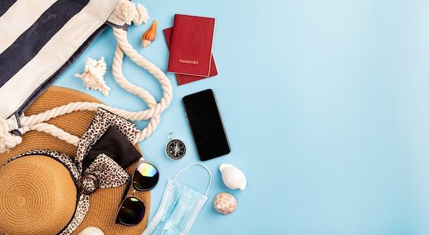Viajes y aventuras objetos de viaje planos con sombrero de verano, teléfono inteligente, pasaporte, gafas de sol y brújula sobre fondo azul con espacio de copia