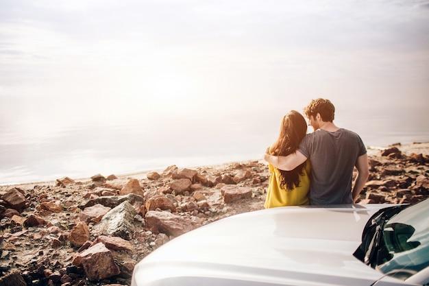 Viajes en coche, turismo - pareja feliz conduciendo por la carretera hacia el atardecer en un coche deportivo