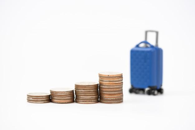 Viajes y concepto de ahorro financiero. equipaje en miniatura, pilas de monedas y pasaporte.