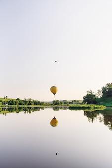 Viajes y deporte. dos globos multicolores de aire caliente volando sobre el lago en el cielo al amanecer.