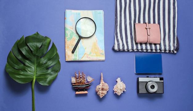 Viajes minimalistas naturaleza muerta estilo plano. accesorios de viajero turístico sobre fondo azul con hoja de monstera tropical