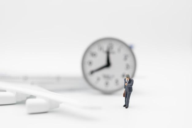 Viajes de negocios, concepto de tiempo. ciérrese para arriba de la figura miniatura del viajero del hombre de negocios con el equipaje de la maleta que mira para mirar con el mini modelo del aeroplano del juguete y el reloj redondo en el fondo blanco.