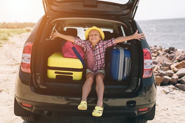 Viajes, turismo - chica con bolsas listas para viajar a las vacaciones de verano. niño en aventura. concepto de viaje en coche