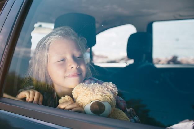Viajes, turismo - chica con osito de peluche listo para el viaje de vacaciones de verano. niño en aventura. concepto de viaje en coche