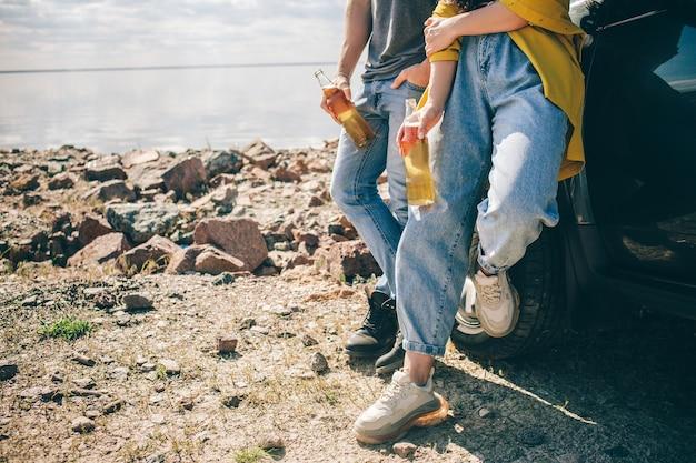 Viajes, turismo - picnic cerca del agua. pareja de aventuras. concepto de viaje en coche. hombre y mujer beben cerveza.