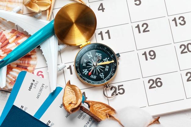 Viajes y vacaciones, brújula en el calendario planificador