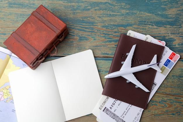 Viajes, viajes de vacaciones, turismo - cierre cuaderno, maleta, avión de juguete y mapa turístico en mesa de madera.