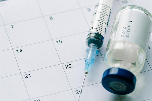 El vial con la vacuna y la jeringa en el calendario.