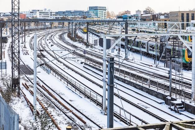 Vías y trenes cubiertos por la nieve en londres.