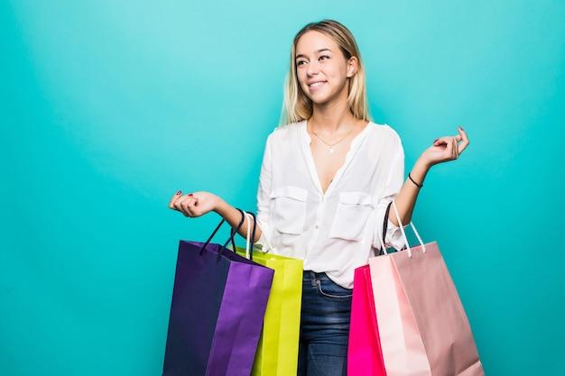 Vibraciones de compras coloridas. retrato de cuerpo entero de una mujer rubia sonriente con coloridas bolsas de la compra en la pared de la menta