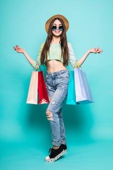Vibraciones de compras coloridas. retratos de cuerpo entero de mujer morena sonriente con sombrero y ropa brillante con bolsas de compras corriendo