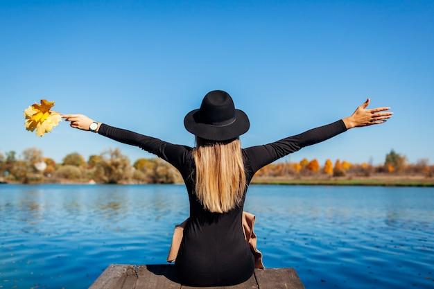 Vibraciones otoñales. mujer joven que se relaja por el río con los brazos levantados sentado en el muelle.