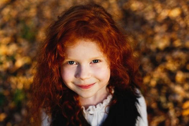 Vibraciones otoñales, retrato infantil. encantadora y roja niña de pelo se ve feliz de pie en el caído