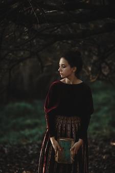 Las vibraciones del otoño. estilo gótico. mujer morena en paño rojo oscuro