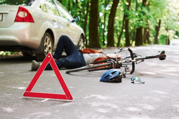 Víctima en el asfalto. bicicleta y accidente de coche de color plateado en la carretera en el bosque durante el día