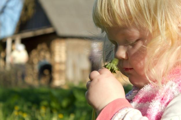 La vida en armonía con la naturaleza - niña oliendo una flor