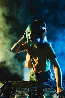 Vida de club nocturno de alto ángulo con humo colorido y dj femenino
