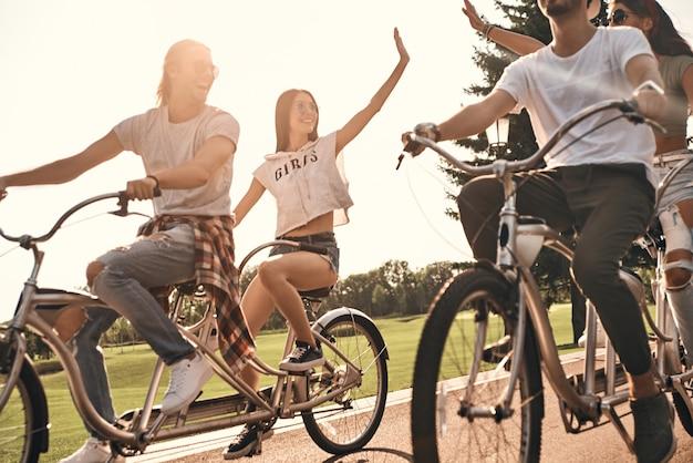 ¡la vida es asombrosa! dos jóvenes mujeres modernas dándose cinco mientras andan en bicicleta con amigos al aire libre