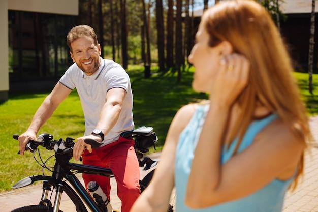 Vida feliz. hombre alegre en bicicleta mientras mira a su esposa y descansa al aire libre