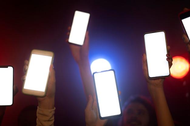 Vida nocturna de gente bailando en un club y sosteniendo teléfonos inteligentes.
