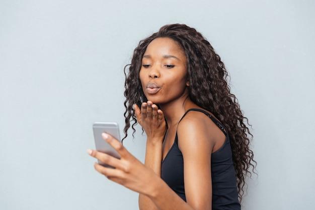 Video chat de mujer afroamericana en smartphone sobre pared gris