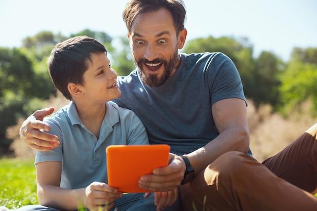 Video divertido. encantador niño feliz sosteniendo una tableta mientras está sentado con su padre en el parque