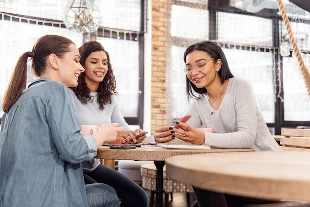Video divertido. hermosos tres amigos felices chismeando mientras miran la pantalla y sonríen