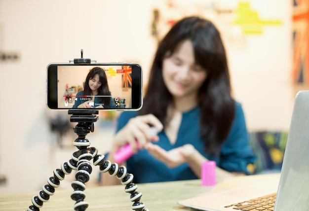 Video en vivo blogger joven vlogger girl transmisión en vivo sobre contenido cosmético a través del móvil