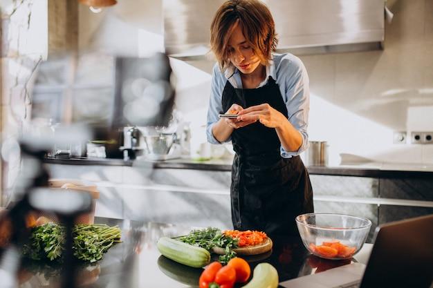 Videoblogger joven cocinando en la cocina y filmando