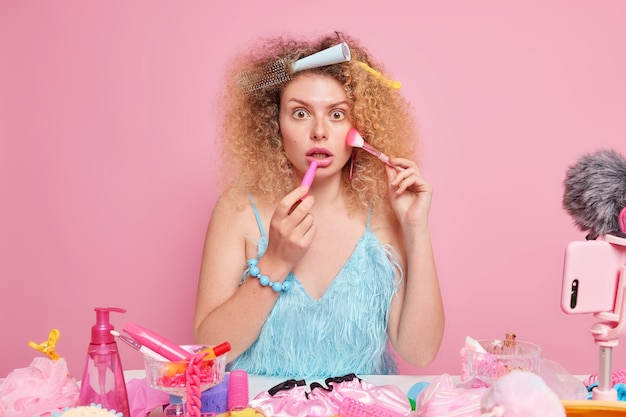 Videoblogger profesional graba video tutorial sobre maquillaje, usos, pincel cosmético, aplica barra de labios, soportes para interiores.