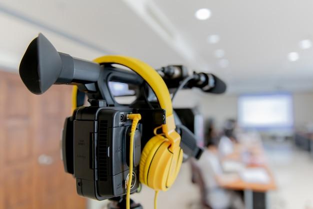 Videocámara en sala de conferencias de negocios, grabación de participantes y auriculares.