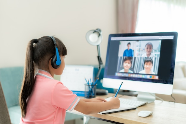 Videoconferencia de una alumna asiática e-learning con profesor y compañeros de clase en la computadora en la sala de estar