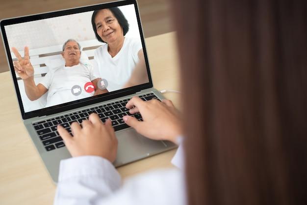 Videoconferencia en línea del médico con el paciente anciano para monitorear y preguntar por los síntomas de la enfermedad.