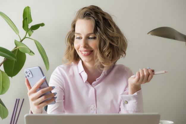 La videoconferencia sonriente de la mujer de negocios joven que llama en teléfono inteligente habla por la webcam en el chat en línea, el servicio de atención al cliente y el concepto de enseñanza en línea a distancia. trabajo remoto
