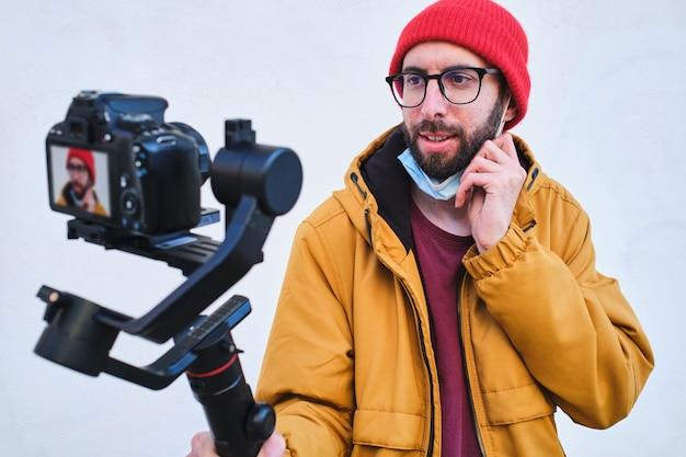 Videógrafo grabando a sí mismo con una cámara réflex digital en un cardán motorizado con máscara protectora