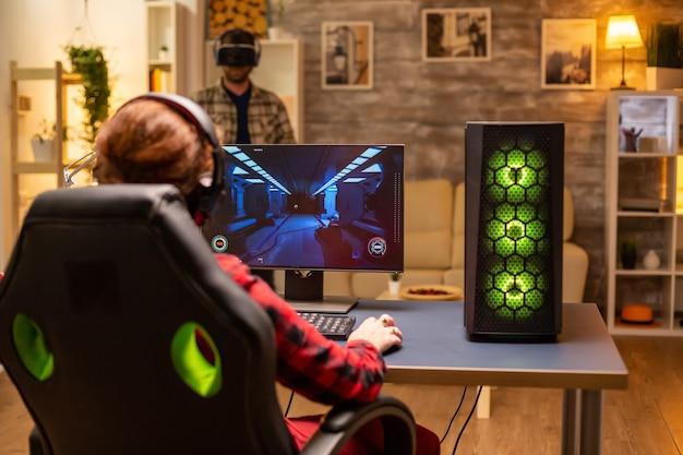 Videojugador profesional femenino jugando un juego de disparos en línea a altas horas de la noche en la sala de estar