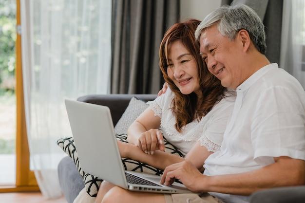 Videollamada asiática mayor de los pares en casa. abuelos chinos mayores asiáticos, usando la videollamada del ordenador portátil que habla con los niños del nieto de la familia mientras que miente en el sofá en concepto de la sala de estar en casa.