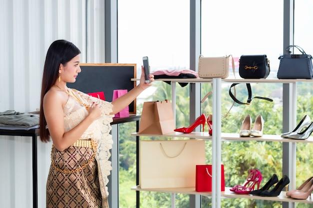 Videollamada hermosa de la mujer con el teléfono en el traje tradicional nacional de tailandia en la tienda shpping.