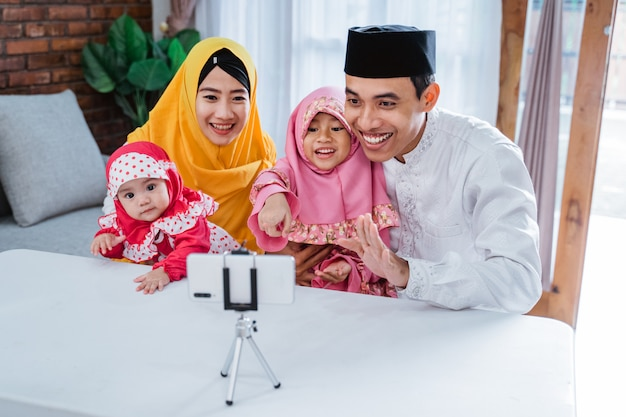 Videollamadas familiares musulmanas asiáticas con familiares durante eid mubarak usando un teléfono móvil