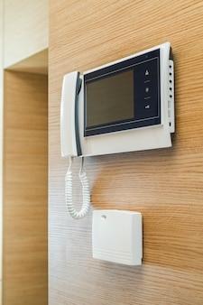 Videoportero con pantalla en la pared de madera