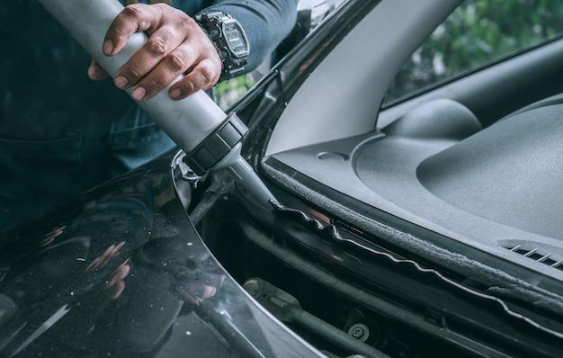 Vidriero de automóviles agregando pegamento en el parabrisas o parabrisas de un automóvil en el garaje de la estación de servicio automático antes de la instalación