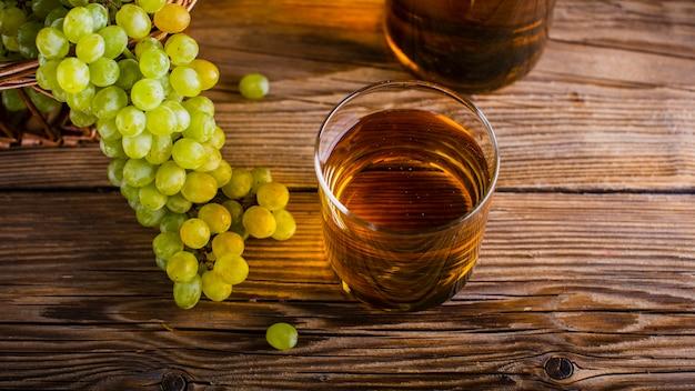 Vidrio de alto ángulo con racimos de uvas naturales